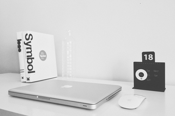 black-and-white-image-of-laptop-computer-mouse-and-book-on-table.jpg